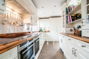kitchen with white painted wooden worktops and white brick tiles